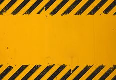 Yellow background with black grunge hazard sign. Old yellow weathered painted background with grunge black hazard sign stripes and copy space royalty free stock photography