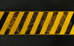Yellow background with black grunge hazard sign. Old yellow weathered painted background with grunge black hazard sign stripes over dark stock image