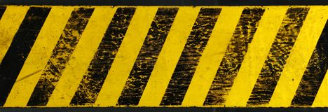 Yellow background with black grunge hazard sign. Old yellow weathered painted background with grunge black hazard sign stripes over dark stock images