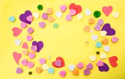 Yellow background with colorful cut out and candy hearts in mostly pinks and purples and a few tiny flowers - Room for text Royalty Free Stock Images