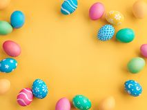 Yellow background with colorful easter eggs. Happy Easter! Yellow background with colorful easter eggs. Top view with copy space Stock Photo