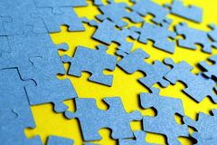 Blue puzzles scattered on a yellow background royalty free stock photography