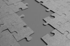 Gray puzzles laid out on the table on a gray background stock image