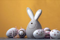 On a yellow background is a group of Easter painted white eggs and a toy bunny. stock images