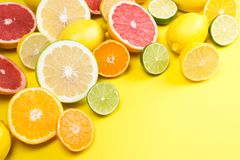 On a yellow background, lie a sliced grapefruit with other fruit lemons, and oranges royalty free stock image