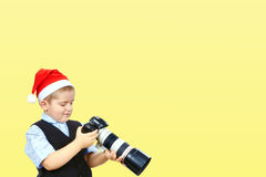 On a yellow background photographer in cap of Santa Claus Stock Images