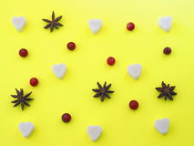 Yellow background with sugar heart, anise stars and cranberries. Top view Stock Photography