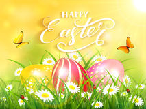 Yellow background with three Easter eggs in grass Stock Photos