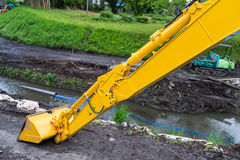 Yellow backhoe loader making canal for flooding prevention Stock Photo