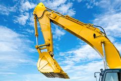 Free Yellow Backhoe With Hydraulic Piston Arm Against Blue Sky. Heavy Machine For Excavation In Construction Site. Hydraulic Machinery. Stock Photos - 153843773