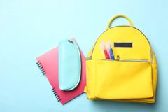 Yellow backpack with different school supplies royalty free stock photo