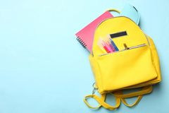Yellow backpack with different school supplies stock image