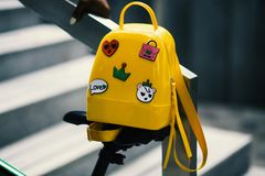 Yellow Backpack With Five Assorted Stickers on Grey Metal Stairway Rail Stock Image