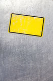 Yellow badge on stainless steel Stock Photo