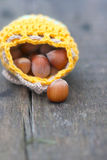 Yellow bag with hazelnut on the old board Royalty Free Stock Photo