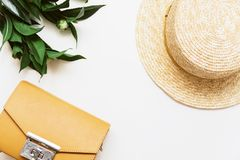 Yellow bag, plant and straw hat on a beige background royalty free stock photo