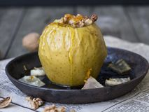 Yellow baked apple with cinnamon, melon, walnuts and honey on a black cast-iron bowl on a wooden background. Autumn or winter dess royalty free stock image