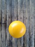 A yellow ball. Yellow ball on a bamboo flooe Royalty Free Stock Image
