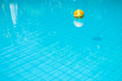 The yellow ball on the blue and clear water pools Royalty Free Stock Photo