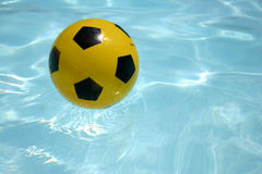 Yellow ball floating. Yellow ball in blue pool Royalty Free Stock Image
