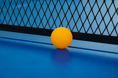 Yellow ball hits the bottom of the net on a blue pingpong table Royalty Free Stock Photography
