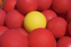 Yellow ball among red balls. One is different from the others. Nice background Royalty Free Stock Image