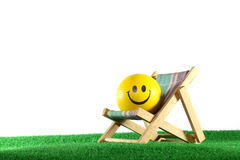 Yellow ball with smile and camp bed. On green grass Royalty Free Stock Image