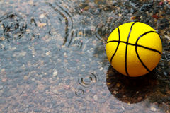 Yellow ball in wet field Stock Photos