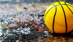 Yellow ball in wet field Royalty Free Stock Photos