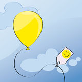 Yellow balloon. With smiley on a label Royalty Free Stock Image
