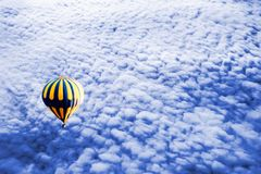 Yellow Balloon above the cumulus blue clouds. Travel concept.  stock image