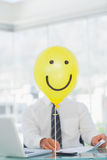 Yellow balloon with cheerful face hiding businessmans face Royalty Free Stock Photos