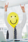 Yellow balloon with cheerful face hiding rock and roll businessm Royalty Free Stock Photography