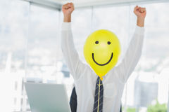 Yellow balloon with cheerful face replacing businessmans face Royalty Free Stock Photography