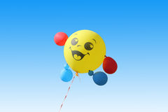 Yellow balloon flying on a blue sky background Stock Image