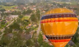Yellow balloon with red and blue stripes in front of the landscape of a German village
