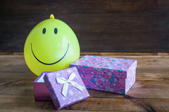 Yellow balloon with smile and gift box Stock Photography