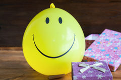 Yellow balloon with smile and gift box Royalty Free Stock Photo