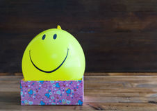 Yellow balloon with smile and gift box Stock Images