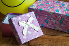 Yellow balloon with smile and gift box Royalty Free Stock Image