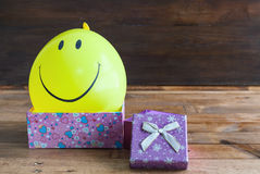 Yellow balloon with smile and gift box Royalty Free Stock Photos