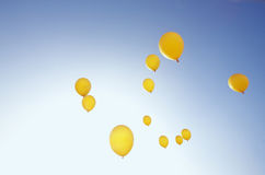 Yellow balloons in sunny blue sky Stock Images