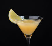 Yellow banana cocktail in martini glass with lemon slice on blac Royalty Free Stock Photo