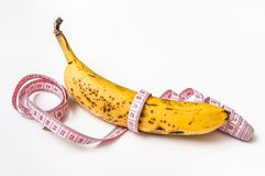 Yellow banana with measuring tape - diet concept Royalty Free Stock Images