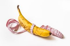 Yellow banana with measuring tape - diet concept Stock Image