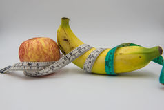 Yellow banana and red apple Measuring tape wrapped around on white background Stock Image