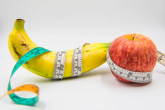 Yellow banana and red apple Measuring tape wrapped around on white background Stock Photos
