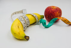 Yellow banana and red apple Measuring tape wrapped around on white background Stock Photography