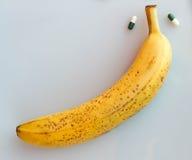 Yellow banana with two pills. Big yellow banana with two pills royalty free stock image