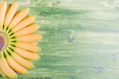 Yellow bananas baby tips up the left fan on green blackboard rig Royalty Free Stock Photos